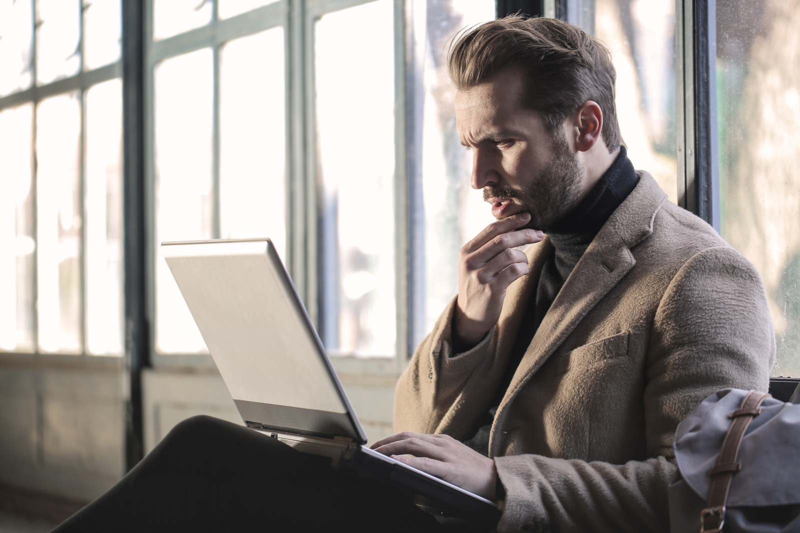 Canva - Man Wearing Brown Jacket and Using Grey Laptop